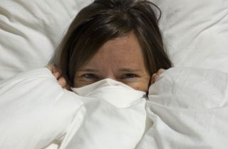 duvet bedding, playful woman peeking out of duvet, goose down duvet, white duvet